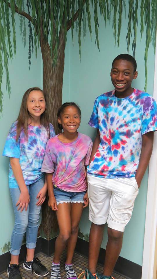 Three campers from ASK's Summer Enrichment Program show off their tie-dye shirts.